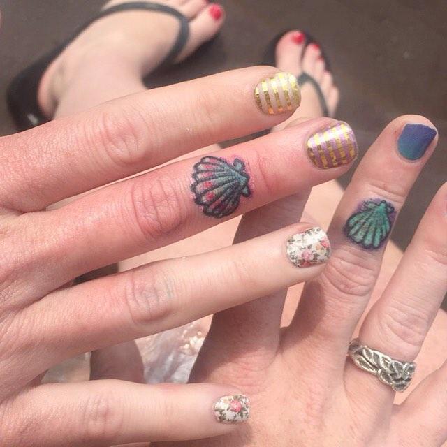 Pequeninas conchas coloridas nos dedos