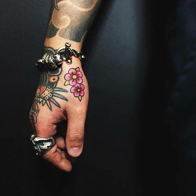 Tatuagem de flores coloridas e vibrantes na mão