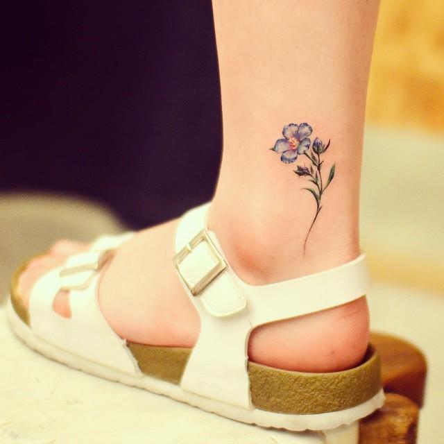 Tatuagem de flor colorida na perna