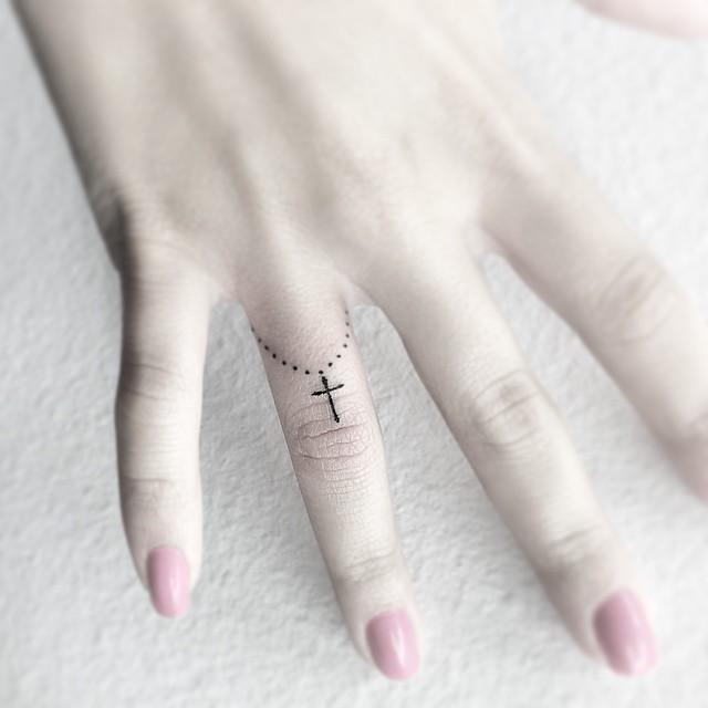 Delicado e pequenino terço no dedo