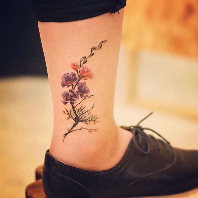 Tatuagem na perna feminina delicada: Flores e arte realista no tornozelo