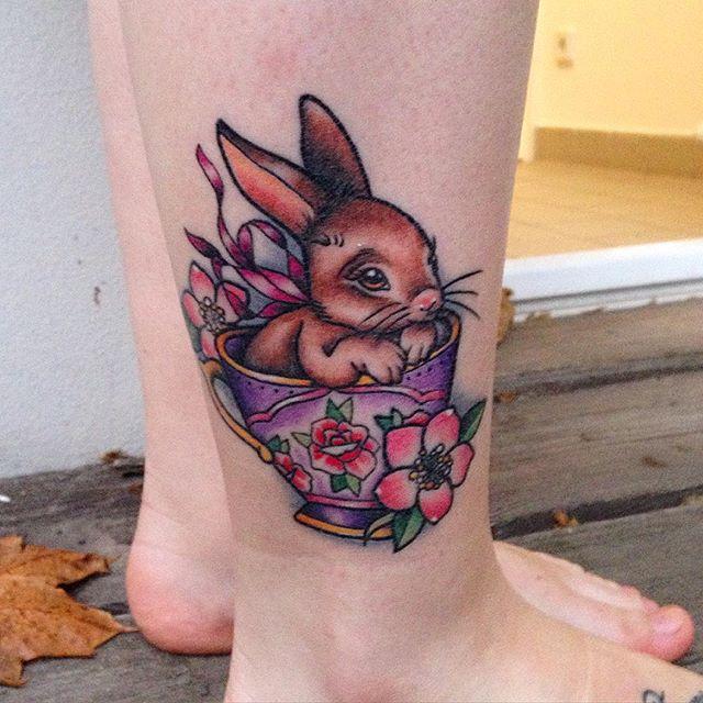 Coelho na xícara, uma tatuagem na perna feminina delicada, com cores chamativas