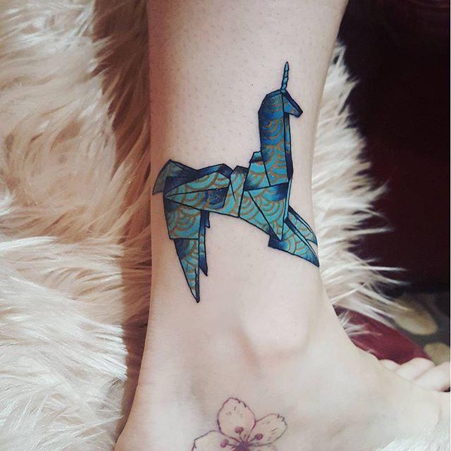 Origami de unicórnio no tornozelo e flor de sakura no pé