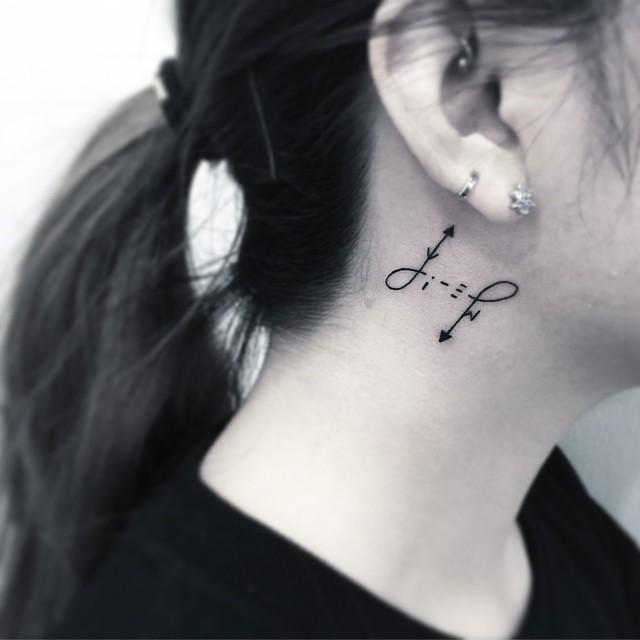 Tatuagem feminina atrás da orelha com motivo discreto.