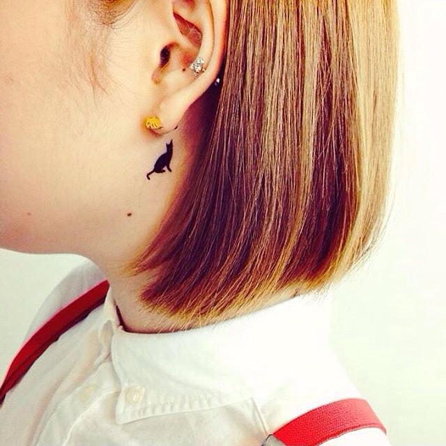 Delicado, o gatinho traz feminilidade para essa tatuagem atrás da orelha.