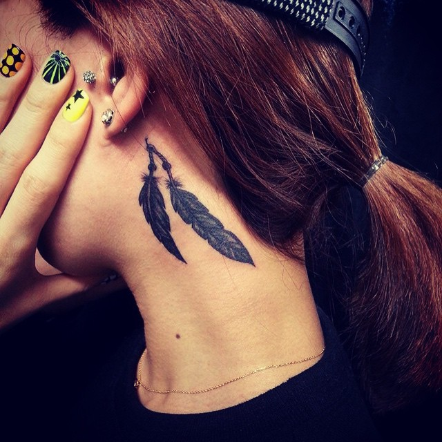 Tatuagem atrás da orelha de penas.