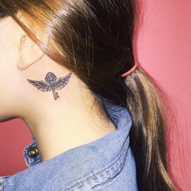 Linda tatuagem feminina atrás da orelha - Uma chave com asas.