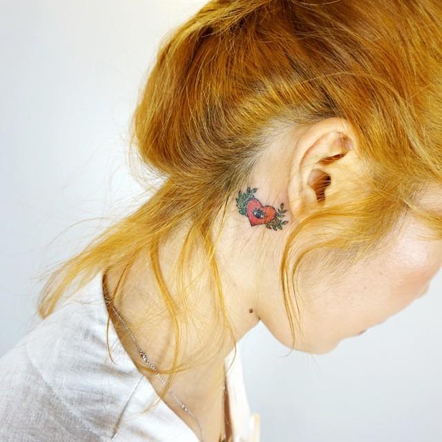 Tatuagem colorida atrás da orelha, um lindo coração com asas, trazendo feminilidade e delicadeza.