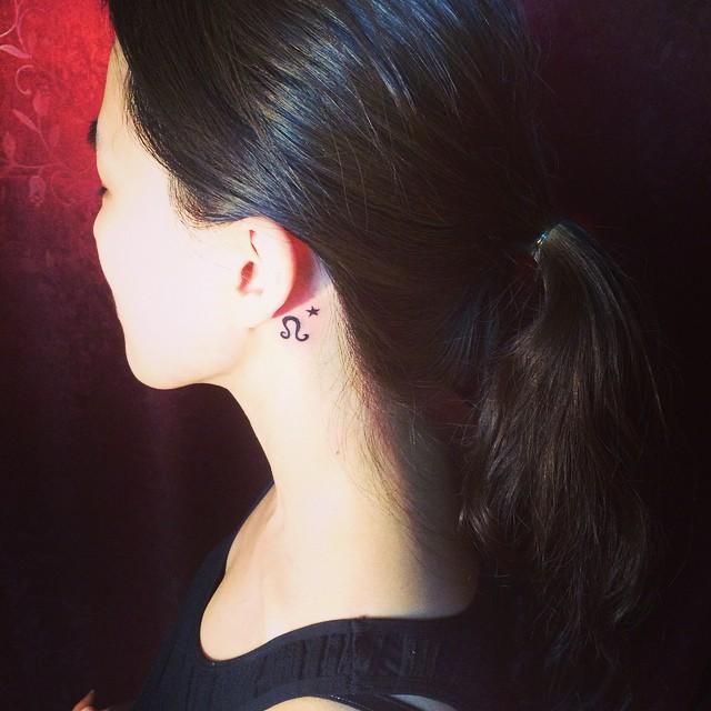 Tatuagem delicada atrás da orelha com motivo zodiacal.