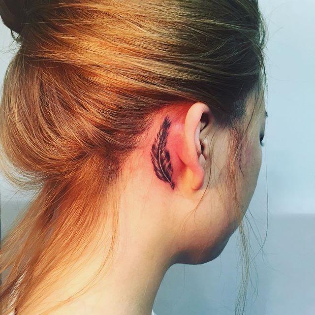 Tatuagem feminina atrás da orelha de uma pena de pássaro.