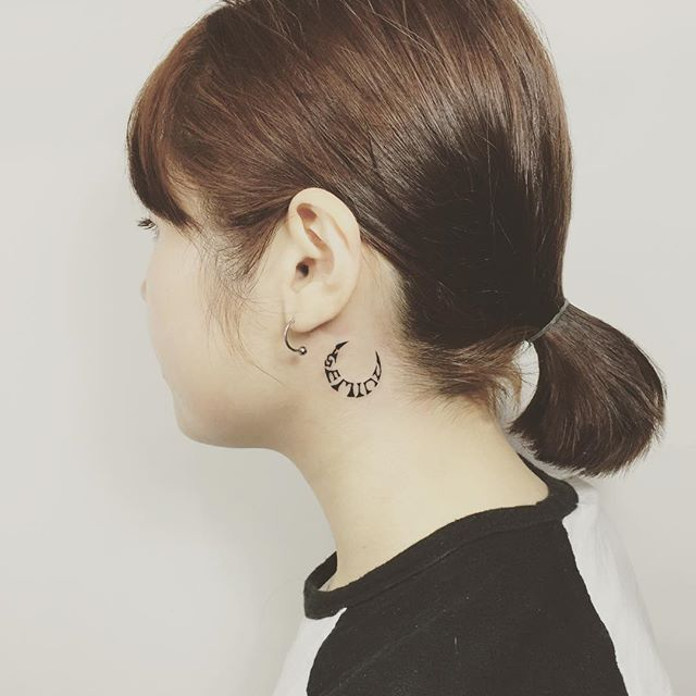tatuagem delicada atrás da orelha com simbologia.