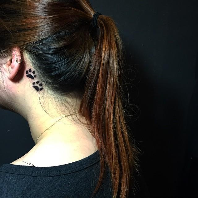 Tatuagem feminina e delicada atrás da orelha - lindas patinha de cachorro.