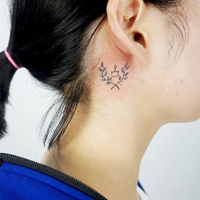 Tatuagem de ramos e coroa atrás da orelha.