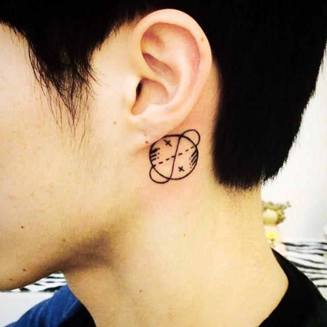 Tatuagem masculina atrás da orelha.