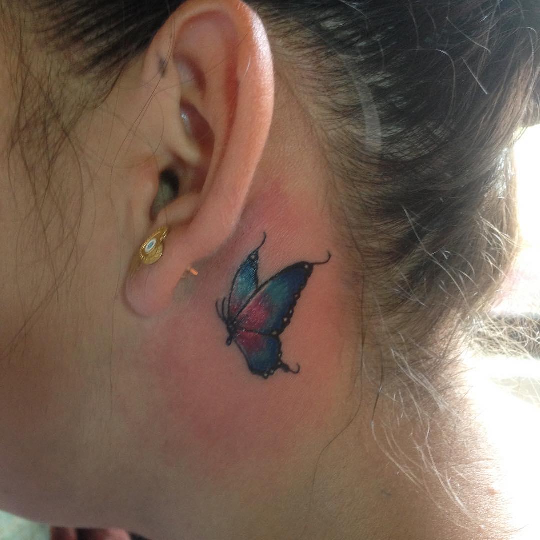 Linda borboleta tatuada atrás da orelha.