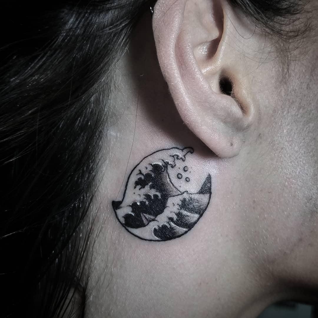 Tatuagem masculina atrás da orelha - uma onda do mar.