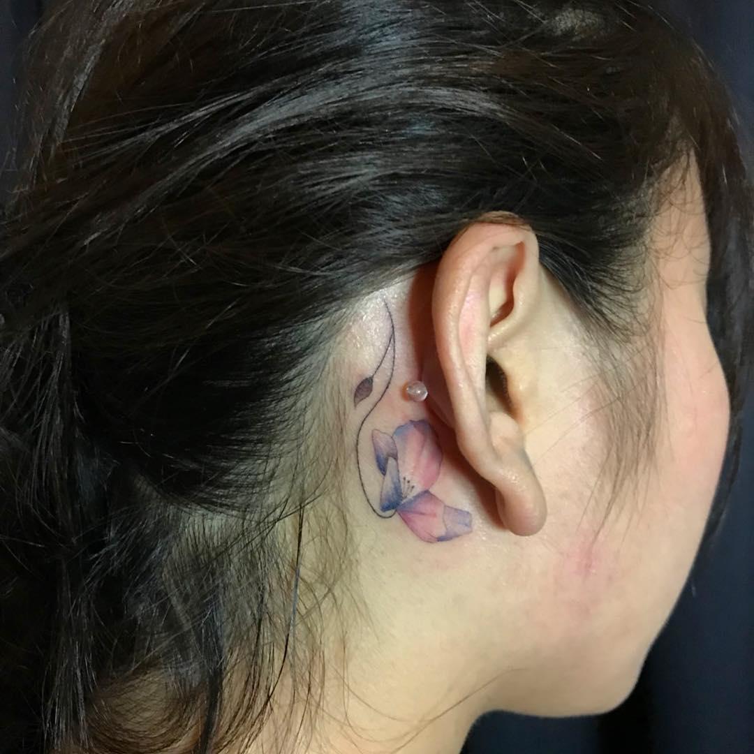 Tatuagem de flor aquarelada atrás da orelha, feminina e delicada.