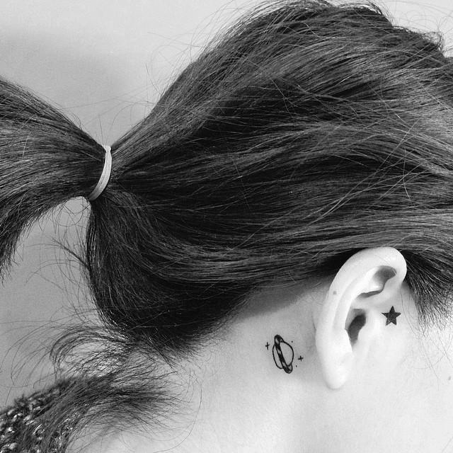 Tatuagem feminina atrás da orelha de um planeta.