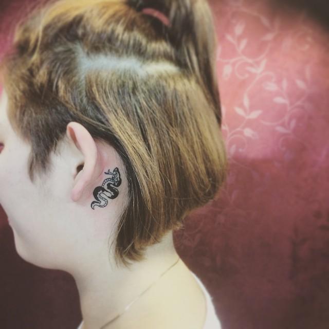 Tatuagem feminina atrás da orelha, para aquelas que preferem algo mais impactante como uma serpente.