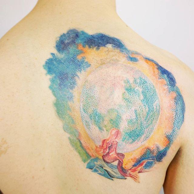 Cheio de cores uma tatuagem para costas masculina: A sereia olhando a lua, seu significado está ligado ao amor e a liberdade