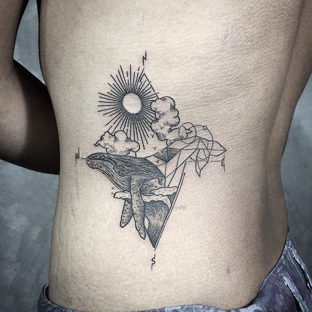 Tatuagem na costela masculina: Desenho abstrato com vários elementos, mas a baleia que há muito tempo foi reverenciada como ancestrais