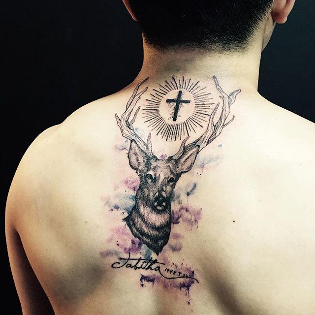 Tatuagem de alce em trabalho aquarela e realismo. Cruz acima irradiada