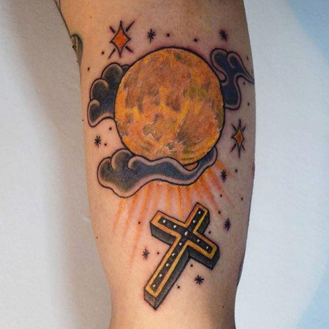 Tatuagem de cruz com adaptações voltada para um trabalho com flores e tons mais escuros