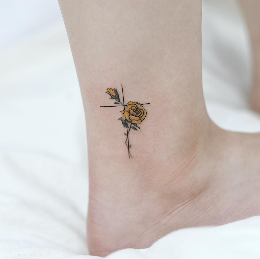 Tatuagem de cruz no tornozelo: Delicadeza pura com rosa amarela