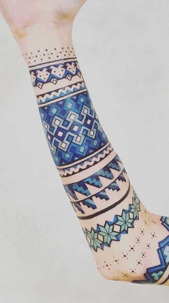 Um conjunto de tatuagens no estilo bracelete que tomam conta do braço inteiro.