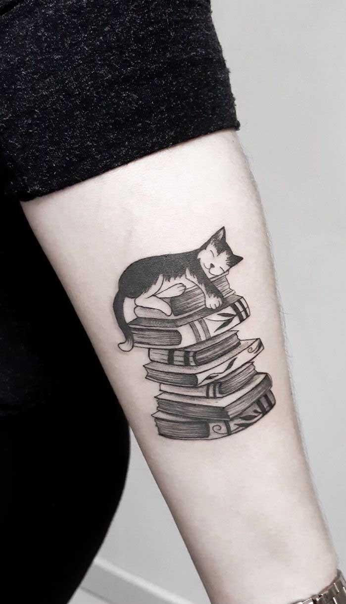 Veja que tatuagem mais fofa do gatinho em cima da pilha de livros.