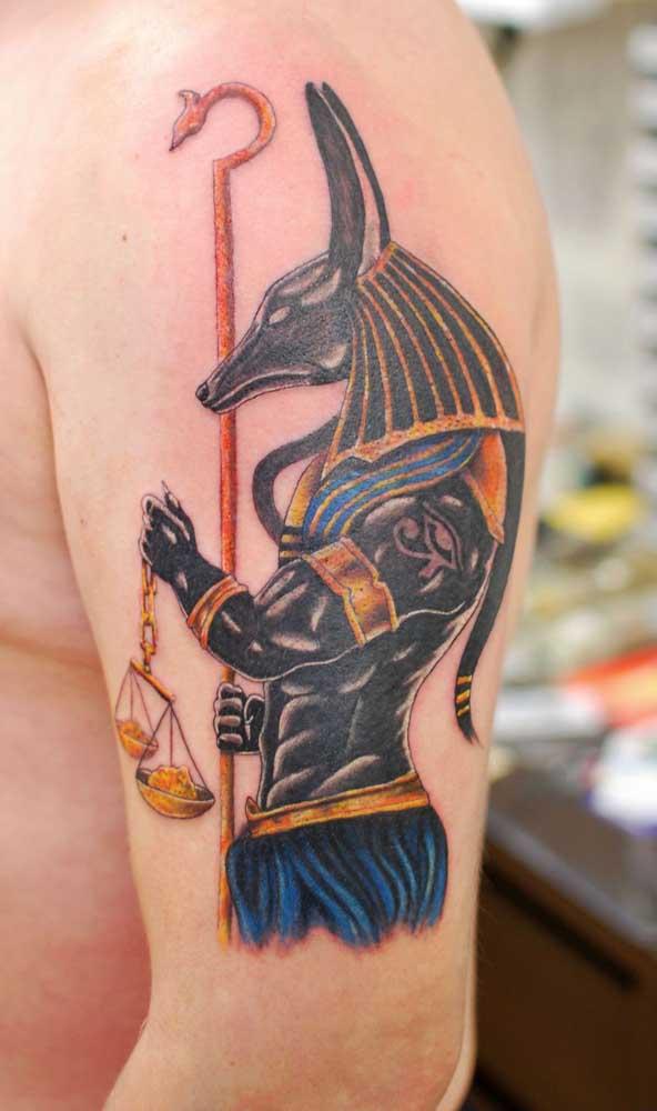 Tatuagem egípcia masculina no braço simbolizando o deus dos mortos, Anúbis
