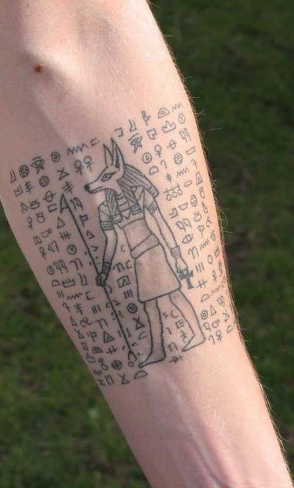 Hieróglifos e o deus Anúbio preenchem o antebraço masculino