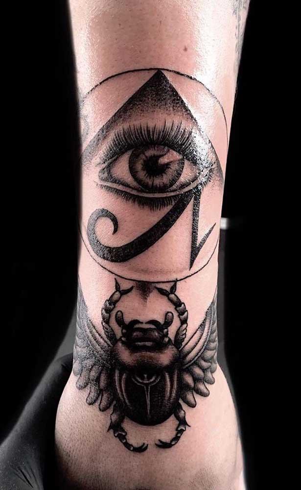 Tatuagem masculina egípcia com escaravelho e olho de Hórus