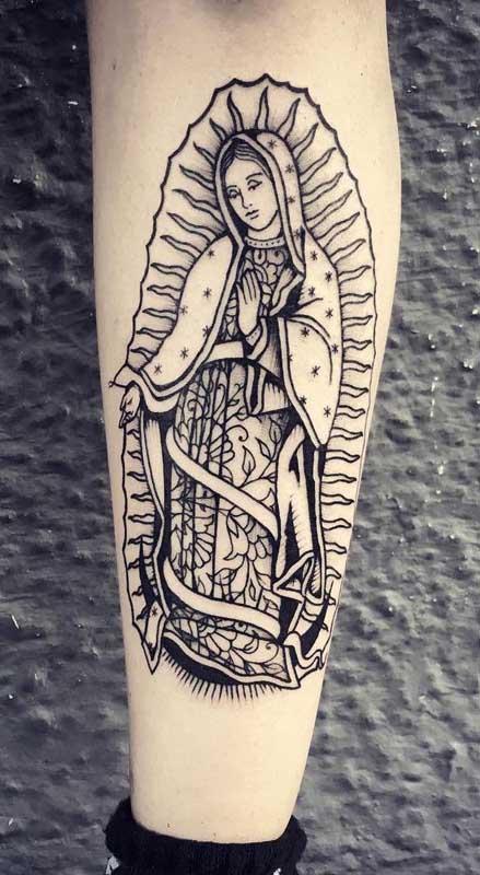 Tatuagem de santa no braço em devoção à Nossa Senhora de Fátima