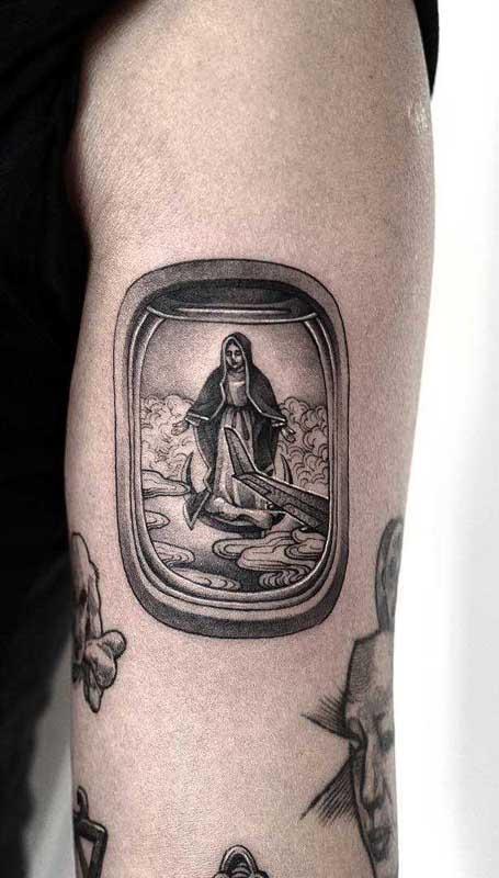 Aqui, a tatuagem de santa vem acompanhada de um cenário completo