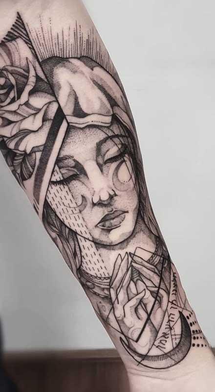 Santa, flores e inscrições marcam essa tatuagem de santa que foge dos modelos mais tradicionais