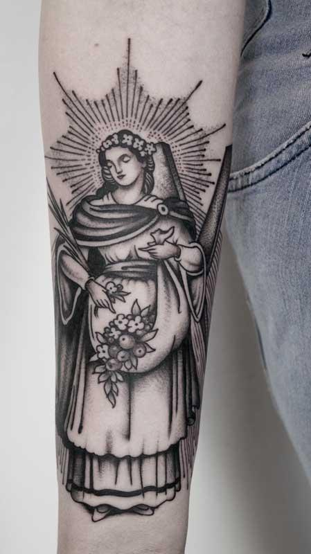 Tatuagem de santa com flores e arco de luz