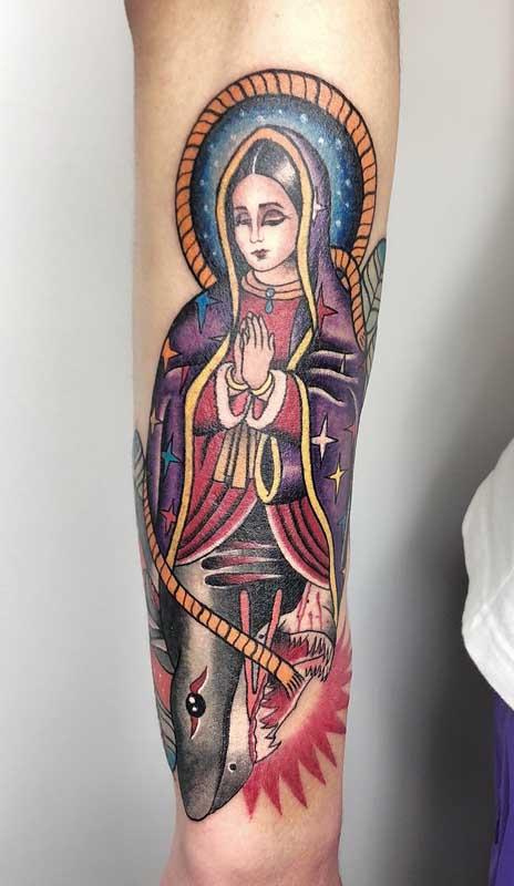 Tatuagem de santa no braço. Repare que a parte de cima traz a imagem da santa, enquanto a parte debaixo é um tubarão