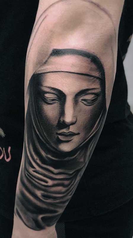 Tatuagem de santa na parte externa do braço. O desenho grande traz ainda mais dramaticidade à figura