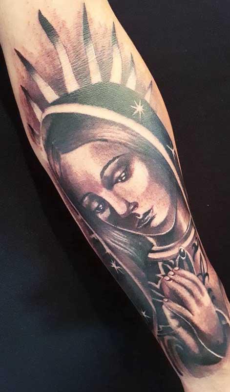 Tatuagem de santa no braço com leves pontos de cor