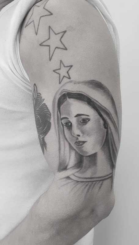 Estrelas e flores complementam essa delicada tatuagem de santa