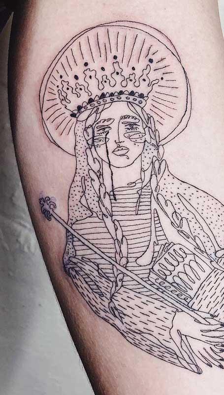 Tatuagem de santa em traços finos e contorno delicado