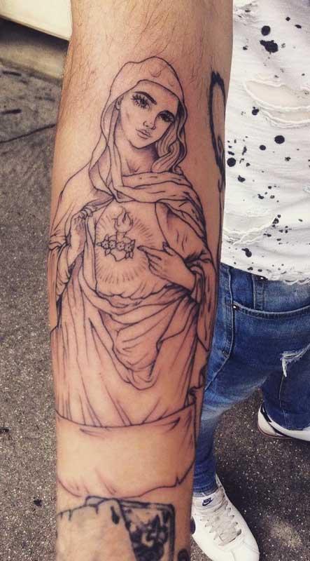 Tatuagem de Nossa Senha de Fátima no braço. O destaque aqui é o traço fino do desenho