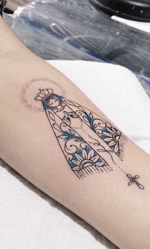 Tatuagem de santa no braço com contorno preto e preenchimento parcial azul