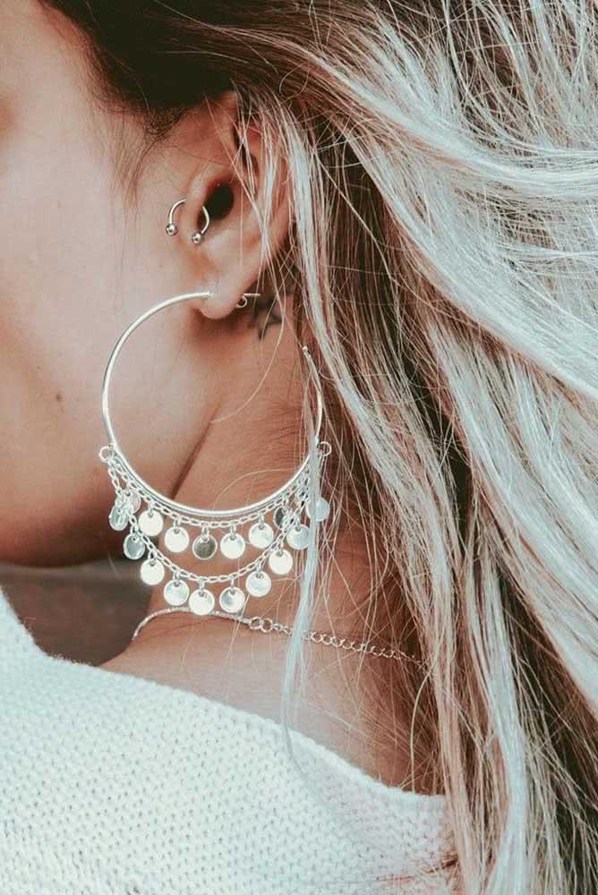 Piercing feminino na orelha tragus e lóbulo