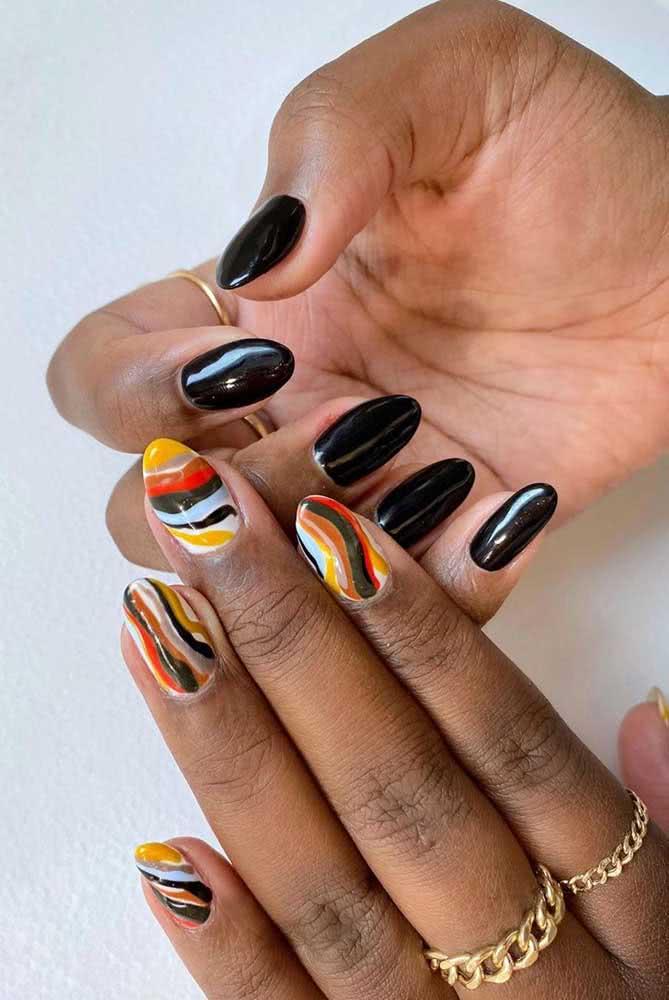 Meio a meio. Para uma mão, o esmalte liso e uniforme, já na outra, as unhas ganham efeito marmorizado em tons étnicos
